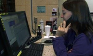 Staff member talking on the phone and using a computer